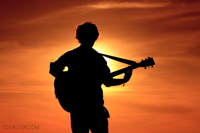 Ant silhouette at sunset with guitar