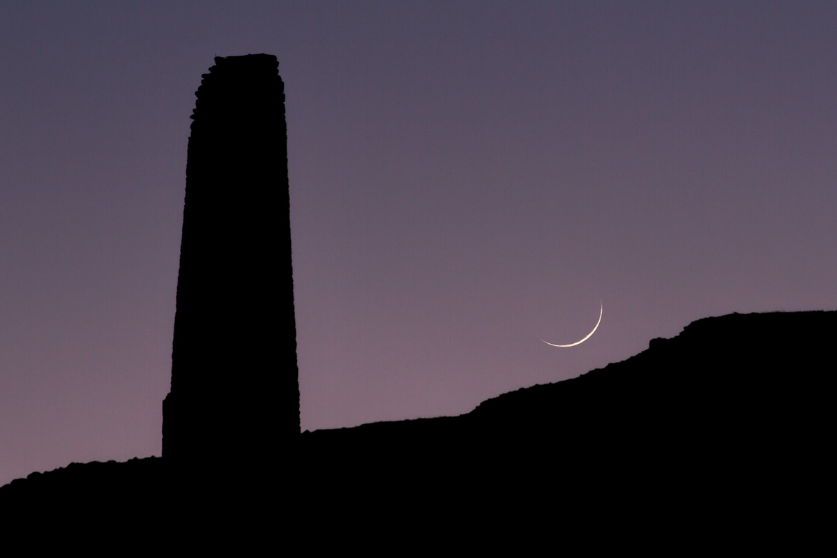 A crescent moon rises over an old engine house chimney on Bodmin Moor