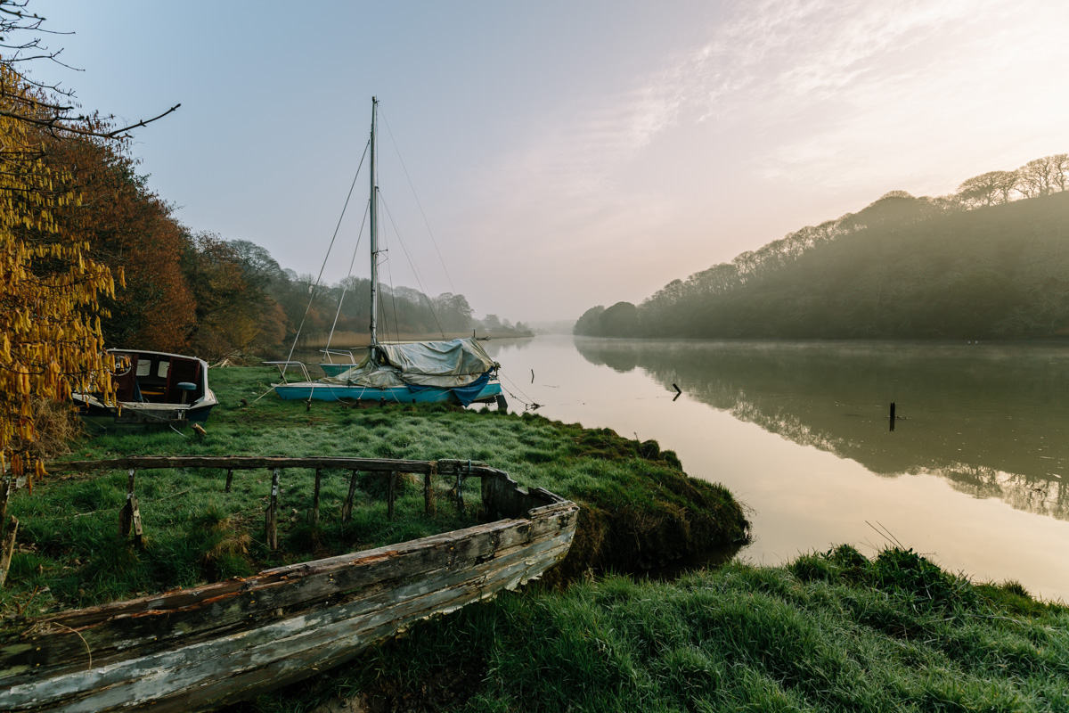 A boat decays in front of a misty morning on the river Truro