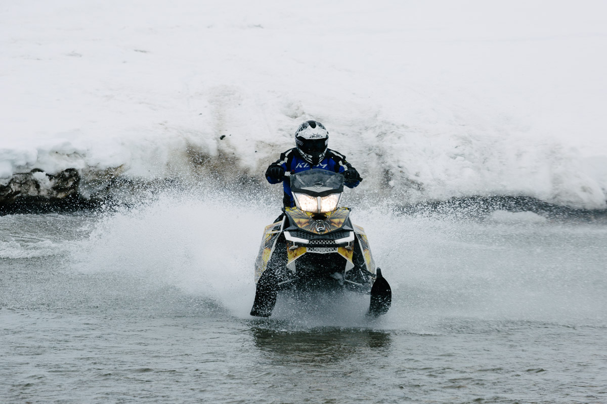 Snow mobile rider tackles the river crossing